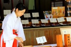 A Woman Creating Calligraphy for a Visitor