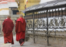 Buddhist Monks strolling around the stupa's prayer wheels